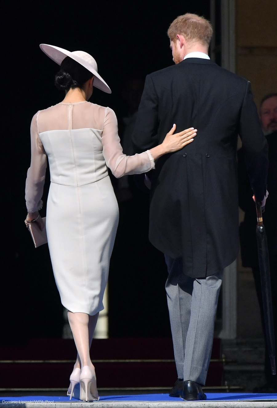Newlyweds Meghan and Harry share a cute moment as they walk out of the party. Meghan places her hand on harry's back.